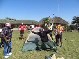 Men cheering in front of tent