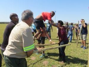 People on poles in field