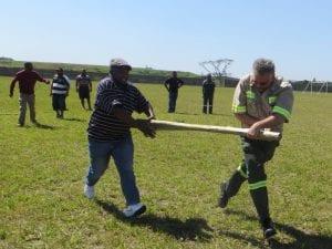 Men carrying poles in field