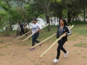 team members carrying wooden poles