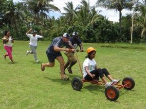 Men pushing woman on cart