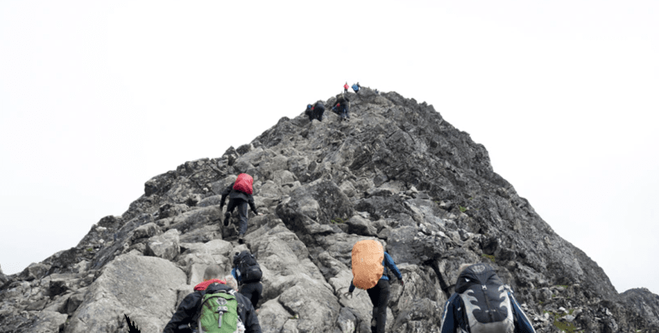5 people ascending a rocky hill