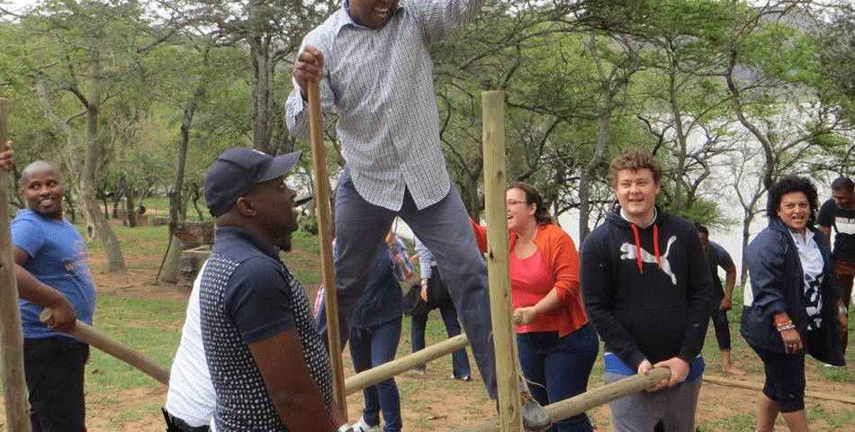 Man being lifted into air at a teambuilding challenge